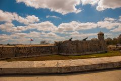 Flag of Cuba against the sky at the fortress wall. The old colonial castle of San Salvador de la Punta. Havana. Cuba.  Royalty Free Stock Photography