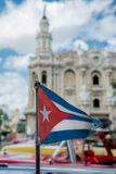 Flag of Cuba with retro cars and Havana historic buildings on ba Royalty Free Stock Images
