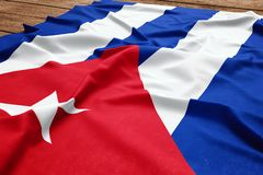 Flag of Cuba on a wooden desk background. Silk Cuban flag top view.  royalty free stock images