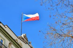 The flag of the Czech Republic on a building with blue sky and the sun in the background. Stock Photos
