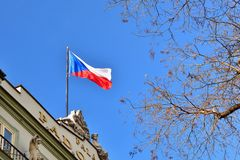 The flag of the Czech Republic on a building with blue sky and the sun in the background. Royalty Free Stock Photo