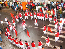 Flag Dance. A group of youngsters dancing with the orange flag in the procession, with onlookers at the side of the street,  ganapati processions. Indian Festive Stock Images