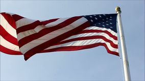 Flag dangles then opens up in wind. Flag waving against blue sky stock footage