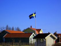 A flag day. A Swedish flag over a village. Typical Swedish wooden houses Stock Photography