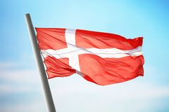 Danish flag. Flag of Denmark against the background of the sky Stock Image