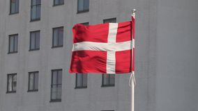 Danish Flag Waving. Flag of Denmark waving in front of a building stock video footage