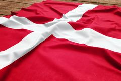 Flag of Denmark on a wooden desk background. Silk Danish flag top view.  royalty free stock photos