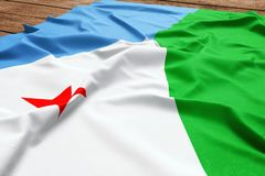 Flag of Djibouti on a wooden desk background. Silk flag top view.  stock images