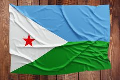 Flag of Djibouti on a wooden table background. Wrinkled flag top view.  royalty free stock images