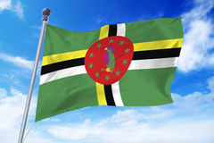 Flag of Dominica developing against a clear blue sky Royalty Free Stock Image