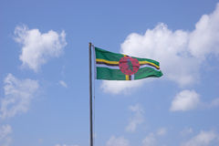 Flag of Dominica. On flagpole over blue sky stock photo