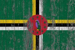 Flag of Dominica painted on worn out wooden texture background.  royalty free stock photography