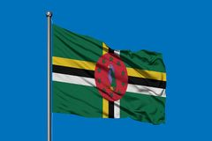 Flag of Dominica waving in the wind against deep blue sky. Dominican flag royalty free illustration