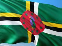 Flag of Dominica waving in the wind against deep blue sky. High quality fabric stock photo