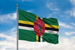 Flag of Dominica waving in the wind against white cloudy blue sky. Dominican flag stock image