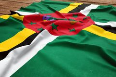 Flag of Dominica on a wooden desk background. Silk Dominican flag top view.  royalty free stock photo