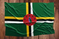 Flag of Dominica on a wooden table background. Wrinkled Dominican flag top view.  royalty free stock image