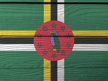 Flag of Dominica on wooden wall background. Grunge Dominica flag texture. royalty free stock image