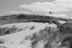 Flag in dunes. American flag on top of sand dunes of cape cod in black and white Stock Image