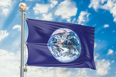 Flag of Earth waving in blue cloudy sky, 3D rendering Stock Photos