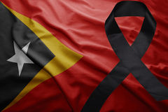 Flag of east timor with black mourning ribbon. Waving national flag of east timor with black mourning ribbon Royalty Free Stock Photo