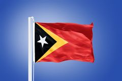 Flag of East Timor flying against a blue sky Royalty Free Stock Photos