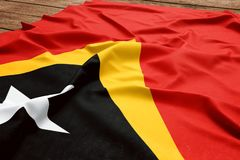 Flag of East Timor on a wooden desk background. Silk East Timorese flag top view.  royalty free stock photo