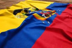 Flag of Ecuador on a wooden desk background. Silk Ecuadorean flag top view.  royalty free stock images