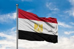 Flag of Egypt waving in the wind against white cloudy blue sky. Egyptian flag stock photography
