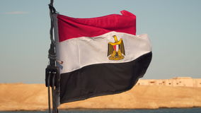 Flag of Egypt on a yacht. In the background the coastline stock footage