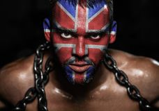 The flag of England on the face of a young man in chains royalty free stock photos