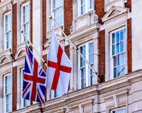 Flag of England and the Union Jack on the Georgian Facade Building in London. Shallow Depth of Field royalty free stock photography