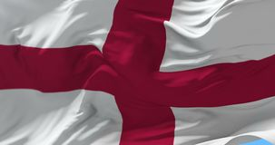 Flag of England waving at wind in blue sky, loop. English flag waving at wind in blue sky, loop stock video