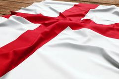 Flag of England on a wooden desk background. Silk English flag top view royalty free stock photos