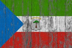 Flag of Equatorial Guinea painted on worn out wooden texture background.  royalty free stock image