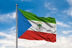 Flag of Equatorial Guinea waving in the wind against white cloudy blue sky.  stock photos