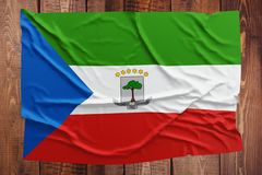 Flag of Equatorial Guinea on a wooden table background. Wrinkled Equatoguinean flag top view.  stock images