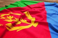 Flag of Eritrea on a wooden desk background. Silk Eritrean flag top view.  stock photography