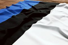 Flag of Estonia on a wooden desk background. Silk Estonian flag top view.  royalty free stock images