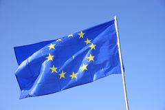 The Flag of Europe, or European Flag flying in blue sky stock photos