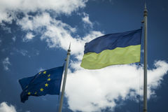 Flag of Europe and Ukraine on flagpoles against the blue sky. Symbols Stock Photos