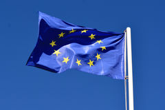 Flag of the European Union. On a bright blue sky lit by the rays of the summer sun Royalty Free Stock Image