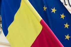 Flag of the European Union covered with the Romanian flag. Political relations and union concept. Close-up view Royalty Free Stock Photo