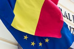 Flag of the European Union covered with the Romanian flag. Political relations and union concept. Close-up view. Flag of the European Union covered with the Stock Images
