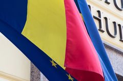 Flag of the European Union covered with the Romanian flag. Political relations and union concept. Close-up view. Flag of the European Union covered with the Stock Image