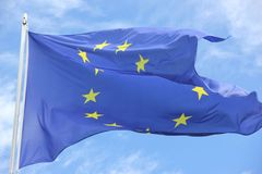Flag European Union. The Flag of the European Union flying in the wind against a blue sky over Europe Stock Photography