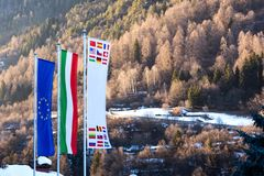The flag of European Union, Italy and other countries are developing against the backdrop of Dolomites in the spring. The flag of the European Union, Italy and stock photos
