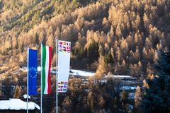 The flag of European Union, Italy and other countries are developing against the backdrop of Dolomites in the spring. The flag of the European Union, Italy and stock photography