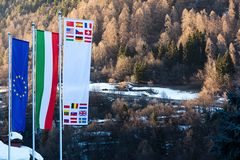 The flag of European Union, Italy and other countries are developing against the backdrop of Dolomites in the spring. The flag of the European Union, Italy and stock photo