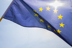Flag of European Union. Sun shining throuhg, sky in the background Royalty Free Stock Images
